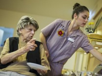 Lopez Leon of Spain assists a resident at breakfast buffet at SenVital elderly home in Kleinmachnow