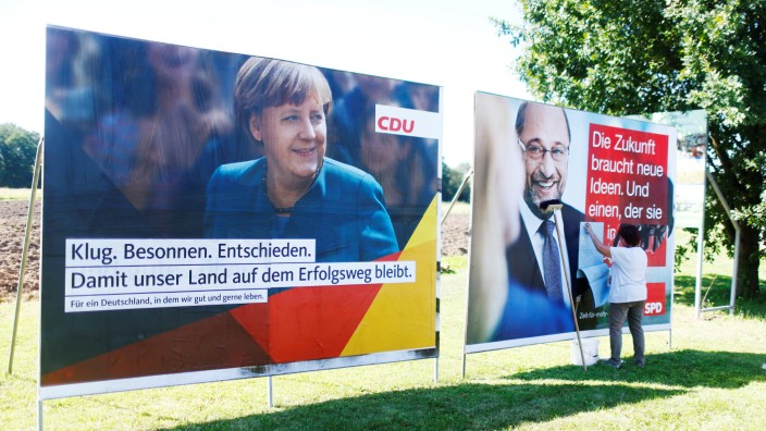 A woman glues poster of the two top candidates for the upcoming general elections, German Chancellor Merkel for the Christian Democratic Union party (CDU), and Schulz for Social Democratic Party (SPD) before an election campaign rally in Bitterfeld-Wolfen