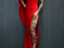 A woman poses with her tattoo during the Shanghai Tattoo Extreme & Body Art Expo 2017 in Shanghai