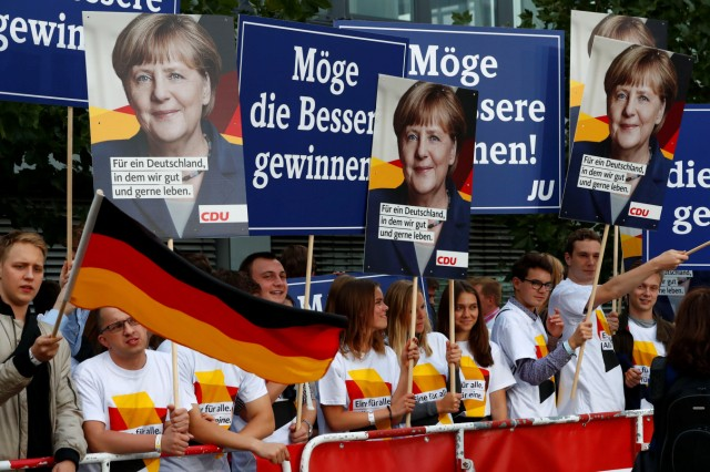 Supporters of German Chancellor Merkel of the CDU hold banners before a TV debate with her challenger Germany's SPD candidate for chancellor Schulz in Berlin