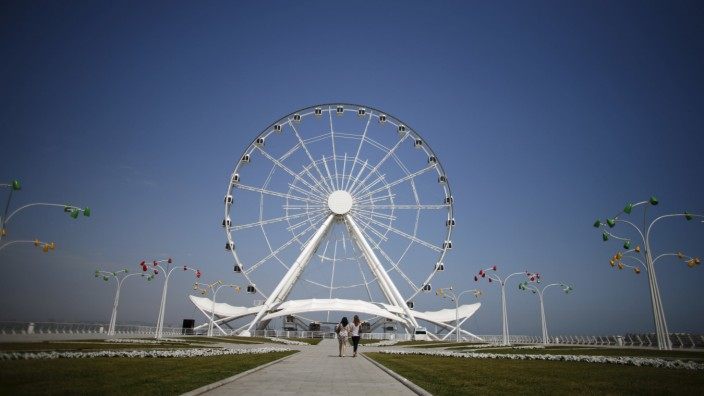 Women walk towards the Baku Ferris Wheel, also known as the Baku Eye, in Baku