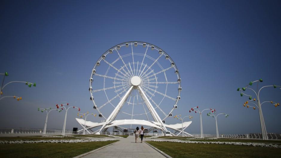 Women walk towards the Baku Ferris Wheel, also known as the Baku Eye, in Baku