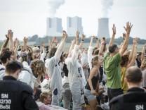 Aktivisten macken Yoga im Polizeikessel vor dem Kraftwerk Neurath Häne zum Himmel und Klatschen Bl