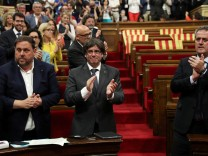 Catalan regional President Carles Puigdemont stands with deputies after voting to hold a referendum  in the Catalonian regional Parliament in Barcelona
