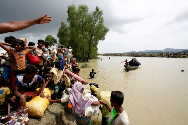 Rohingya refugees wait for boat to cross a canal after crossing the border through the Naf river in Teknaf, Bangladesh