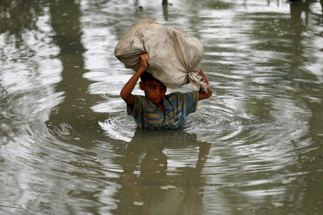 A Rohingya refugee boy walks through water with his belongings after crossing border by boat through the Naf River in Teknaf, Bangladesh