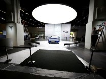 FILE PHOTO: People run preparations at the Tesla company booth during the media day at the Frankfurt Motor Show (IAA) in Frankfurt