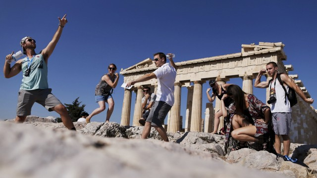 A group of tourists takes a selfie in front of the temple of the Parthenon atop the Acropolis in Athens; WIR