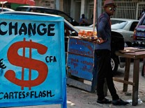 A man stands at a money exchange stall in Kinshasa