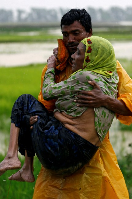A local man carries an old Rohingya refugee woman as she is unable to walk after crossing the border, in Teknaf
