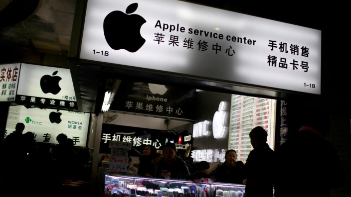 FILE PHOTO: Customers and sales persons are seen at an Apple maintenance service store at a mobile phone market in Shanghai