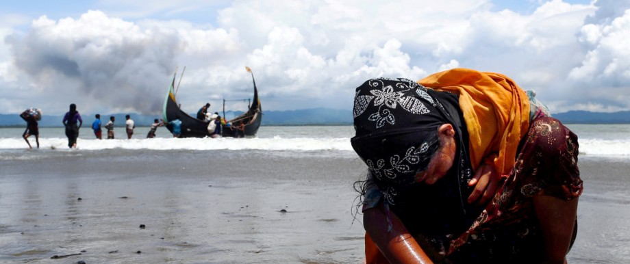 An exhausted Rohingya refugee woman touches the shore after crossing the Bangladesh-Myanmar border by boat through the Bay of Bengal, in Shah Porir Dwip
