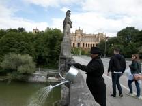 Kunstperformance Overflow Isargiessen, Maximilianeum/Maximiliansbrücke. Die Künstler schöpfen Wasser am Brunnen vor dem Maximilianeum und gießen es auf der Brücke wieder aus. Einer auf der einen Seite, eine auf dieser Seite, und schreiten dann immer