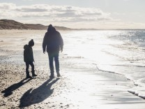 Denmark Hirtshals father and son walking on beach in backlight model released Symbolfoto property