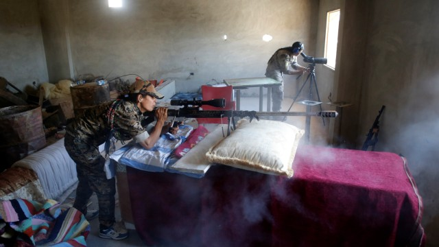 A female Kurdish fighter from the People's Protection Units (YPG) fires a long range sniper rifle at Islamic State militants in Raqqa