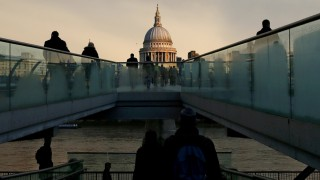 FILE PHOTO: City workers walking towards St Paul's Cathedral as they cross the Millennium footbridge during sunrise in London