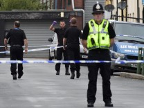 Officers stand behind police cordon after three men were arrested in connection with an explosion on the London Underground, in Newport, Wales