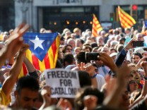 A crowd of protesters gather outside the Catalan region's economy ministry after junior economy minister Josep Maria Jove was arrested by Spanish police during a raid on several government offices, in Barcelona