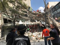 People work at the site of a collapsed building after an earthquake hit in Mexico City, Mexico