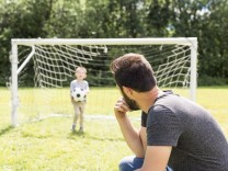 Young father with his little son playing football on football pitch; SZ-Magazin