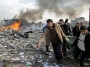 Rauch steigt im Flüchtlingslager Buriej auf, während Palästinenser ein Opfer der Luftangriffe wegtragen. Foto: AFP