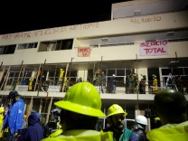 Rescue workers, soldiers and journalists stand near signs reading 'Helicopter leave,' 'No drones' and 'Total silence' during a search for students at the Enrique Rebsamen school after an earthquake in Mexico City