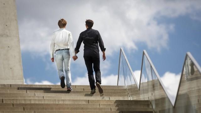 Gestellte Aufnahme 2 Maenner gehen Hand in Hand eine Treppe hinauf Model Release vorhanden model