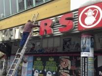 A worker removes a logo of Kaiser's Tengelmann branch in Berlin