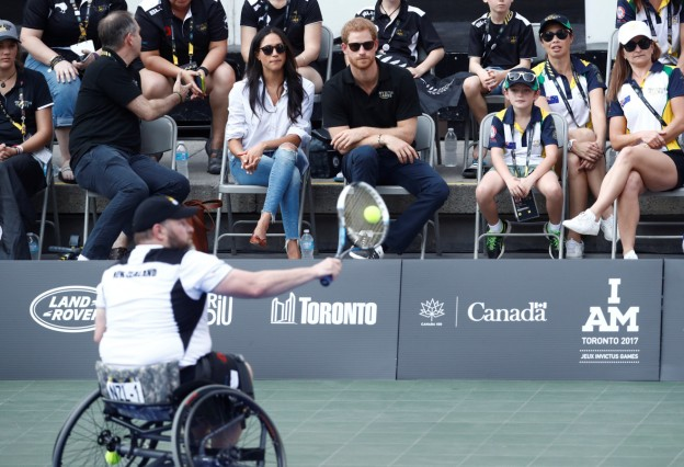 Britain's Prince Harry sits with girlfriend actress Markle to watch a wheelchair tennis event during the Invictus Games in Toronto