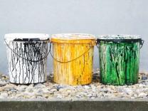 Farbeimer in den Farben schwarz gelb und grün der Parteien