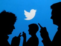 FILE PHOTO: People holding mobile phones are silhouetted against a backdrop projected with the Twitter logo