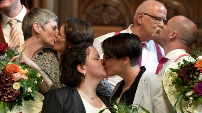 Same-sex couples kiss their partners after get married during a media call at the town hall after the German parliament approved marriage equality in a historic vote this summer, in Hamburg
