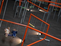 Two visitors ride on swings which form part of the new installation 'One Two Three Swing!' by Danish art collective SUPERFLEX, at the Tate Modern in London, Britain