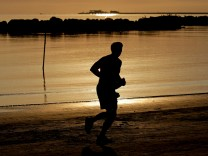 A man runs at sunrise along the beach in Rimini