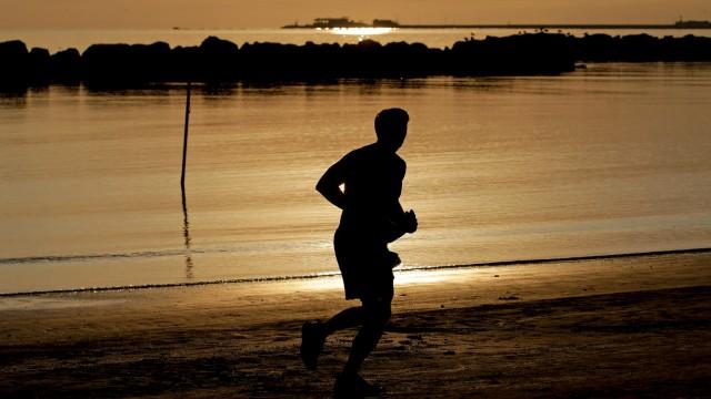 A man runs at sunrise along the beach in Rimini