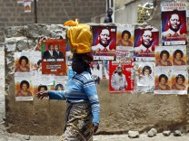 A woman carries a plastic bag on her head as she walks past a wall with various campaign posters on a street in Nairobi