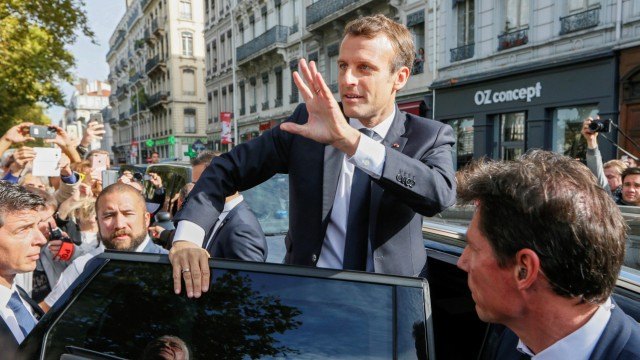 French President Macron waves to supporters during his visit in Lyon