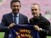 FC Barcelona captain Andres Iniesta holds up a jersey with FC Barcelona's President Josep Maria Bartomeu after announcing the agreement of a contract for life with FC Barcelona, in Barcelona