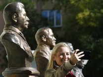 A woman takes a selfie while standing in front of the busts of Soviet leader Stalin and Soviet state founder Lenin at the Alley Of Rulers in Moscow