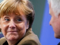 FILE PHOTO:  German Chancellor Merkel smiles to Bavarian state premier and leader of the Christian Social Union Seehofer during news conference in Berlin