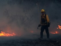 A firefighter works to put out hot spots on a fast moving wind driven wildfire in Orange, California