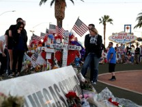 People look over 58 wood crosses, with the names and photos of the October 1 mass shooting victims, in the median of Las Vegas Boulevard South near the 'Welcome to Las Vegas' sign in Las Vegas
