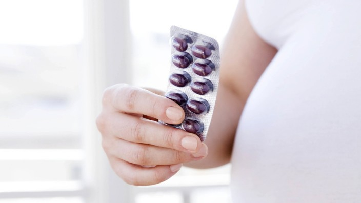 Prenatal vitamins MODEL RELEASED Prenatal vitamins Pregnant woman holding a packet of vitamins Sh