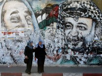 Palestinian students stand in front of a mural depicting late Hamas leader Ahmed Yassin and late Palestinian leader Yasser Arafat, in Gaza City