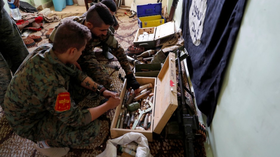 Fighters of Syrian Democratic Forces inspect weapons and munitions recovered at the former positions of the Islamic State militants inside a building at the frontline in Raqqa