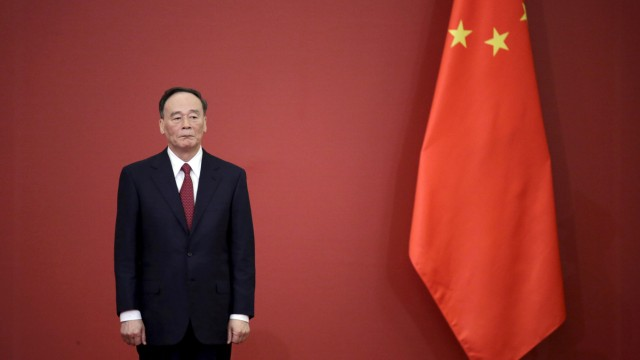 FILE PHOTO: China's Politburo Standing Committee member Wang Qishan stands next to a Chinese flag in Beijing
