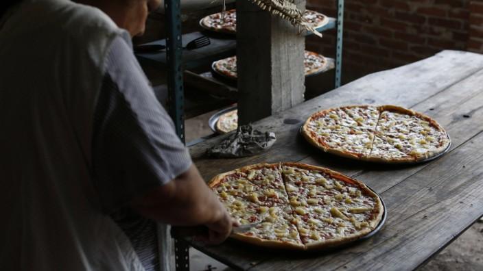 Eine Pizzabäckerin holt Pizza aus dem Ofen.