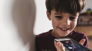 Smiling boy with brown hair standing indoors holding smartphone Smiling boy with brown hair standi