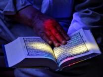 A man reads the Koran at the shrine of Sheikh Abdul Qadir Jeelani, a Sufi saint, during the Muslim fasting month of Ramadan in Srinagar