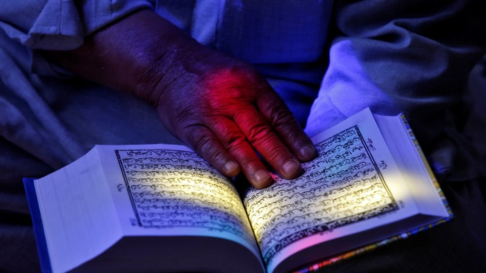 A man reads the Koran at the shrine of Sheikh Abdul Qadir Jeelani, a Sufi saint, during the Muslim fasting month of Ramadan in Srinagar
